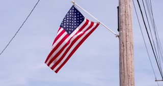 American Flag blowing in wind off telephone pole 4k