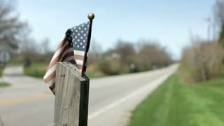 American Flag on post next to country road