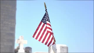 American Flag pan shot with graveyard headstone in background 4k