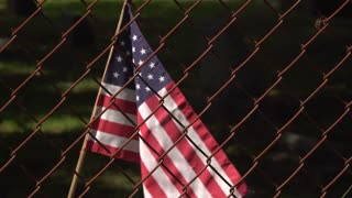 American flag waving behind chain link fence 4k