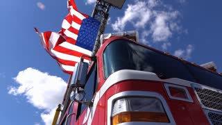 American flag waving in wind hanging from firetruck pan 4k