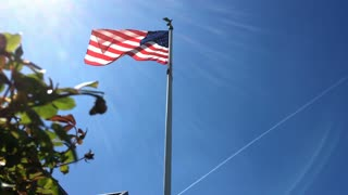 American Flag waving proud in the wind and sunshine jib shot 4k