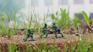 Army men in grass with smoke blowing by