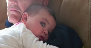 Baby resting head on shoulder with eyes open 4k