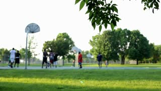 Background in park of people playing basketball