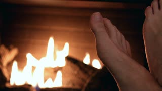 Bare feet warmed in front of fire