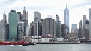 Barge going through East River with downtown Manhattan buildings 4k