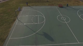 Basketball court with young boy practicing shots aerial 4k