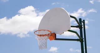 Basketball rim in sunshine on blue cloudy sky 4k