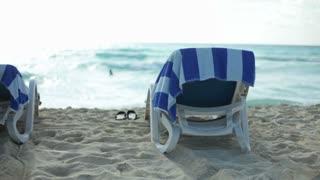 Beach chair and flip flops by ocean