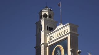 Bellagio Hotel and Casino entrance sign with American Flag waving 4k