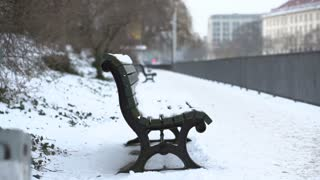 Bench in city covered with snow