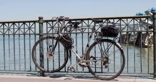Bike locked to railing on pier sidewalk 4k.