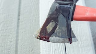Blood dripping of ax of a killer in front of the shed slow motion