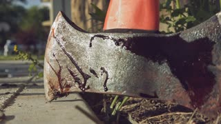 Bloody ax picked up from side of house slow motion