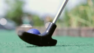 Blue ball at mini golf course hit by club