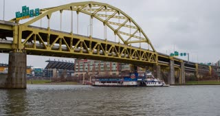 Boat cruise line going under bridge in downtown Pittsburgh 4k