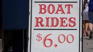 Boat rides pricing sign on sidewalk 4k