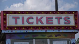 Booth selling tickets for rides at carnival on sunny day 4k