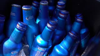 Bottle of Bud Light beer in ice cooler pan shot 4k