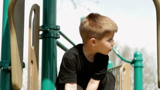 Boy at top of slide in playground