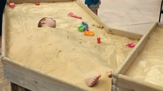 Boy buried in sand getting up