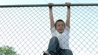 Boy climbing down large fence