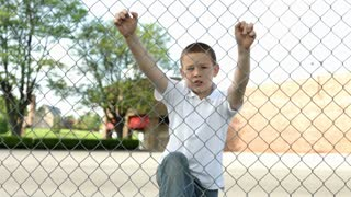 Boy climbing up large fence