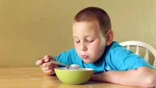 Boy eating a bowl of cereal smiles