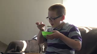 Boy eating bowl of cereal in living room