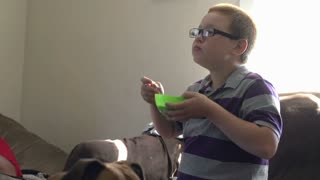 Boy eating bowl of cereal on couch