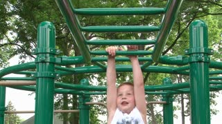 Boy falling while going across Monkey Bars