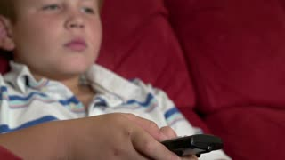 Boy flipping through TV station with remote