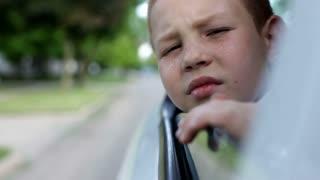 Boy hanging head from car window