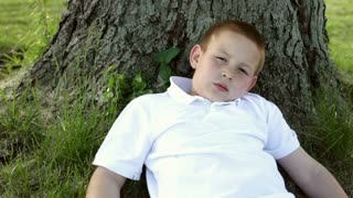 Boy laying in grass against tree