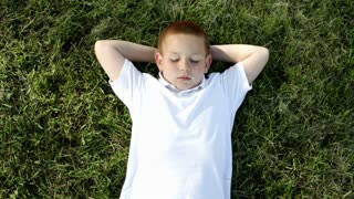 Boy laying in grass with eyes closed