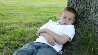 Boy looking around while laying in grass by tree