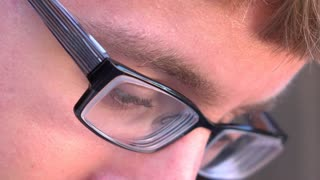 Boy looking down with glasses on reading text messages 4k