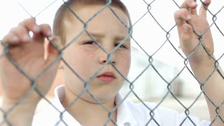 Boy looks upset at camera behind fence