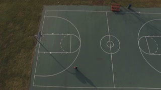 Boy missing shots on basketball court aerial view 4k