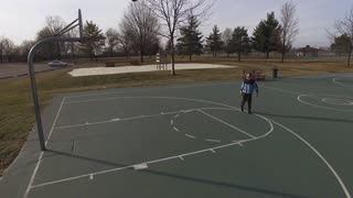 Boy on basketball court shooting practice shots aerial view 4k