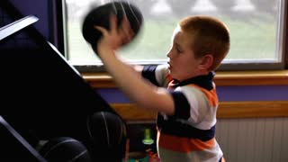 Boy playing arcade game of basketball