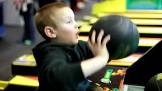 Boy Playing Basketball Game at Arcade