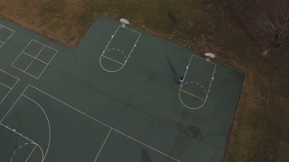 Boy playing basketball on court outdoors aerial shot 4k