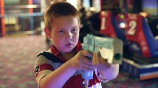 Boy playing Shooting Arcade Game