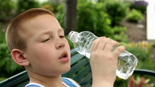 Boy pouring bottle of water into mouth