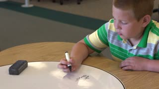 Boy practicing math at dry erase table