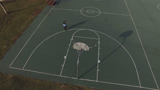 Boy practicing shots on basketball court aerial shot 4k