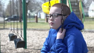 Boy removes glasses while sitting on swing