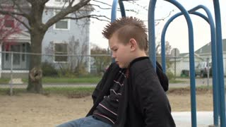 Boy sad and thinking while sitting on merry go round